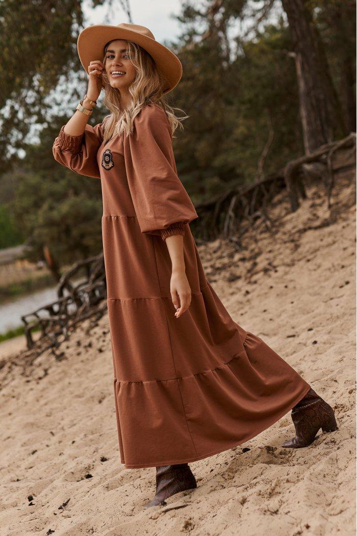 Długa sukienka dresowa z bufiastymi rękawami i ozdobną aplikacją karmelowa M690